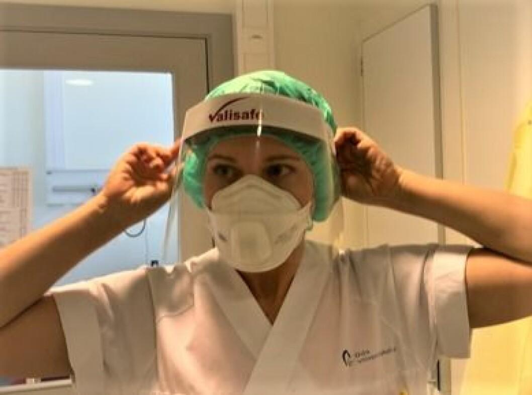 Fysioterapeut Kaia Marie Nicolaisen går med fullt smittevernutstyr hele dagen. Her er hun i ferd med å ta på seg utstyret som beskytter ansikt og hode, før smittefrakken kommer på. (Foto: privat)