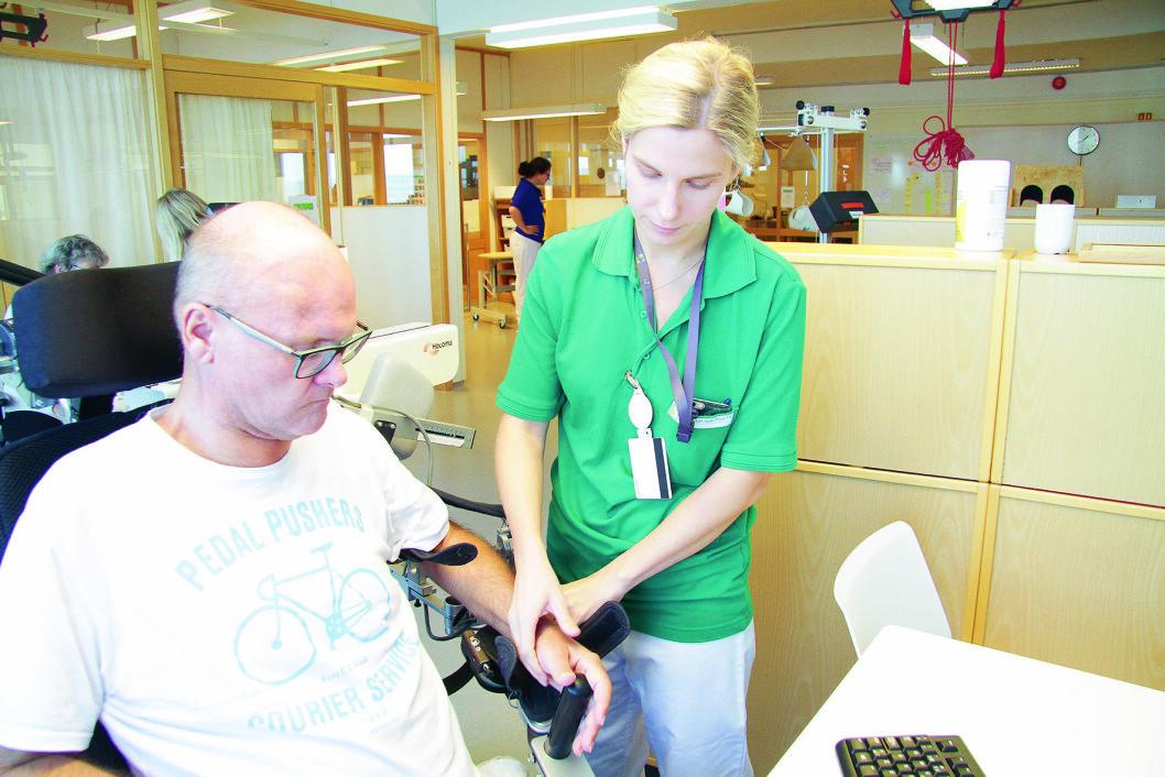 Torgald Sørli får hjelp av ergoterapeut Hanna Sandve når han benytter robotteknologi i treningen. (Foto: Kai Hovden)