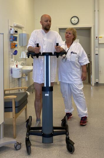 Spesialfysioterapeut Strøm følger med en svimmel pasient dagen etter operasjonen.